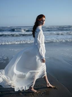 Uma mulher em um vestido branco caminha na areia molhada na costa do oceano