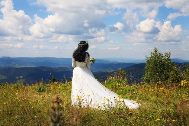 Uma mulher em um vestido branco caminha nas montanhas.