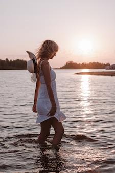 Uma mulher em um vestido branco no fundo do pôr do sol uma bela jovem loira em um verão branco ...