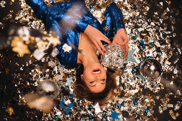 Uma mulher em um vestido de lantejoulas azul sorri e deita no chão sob um confete multicolorido caindo.