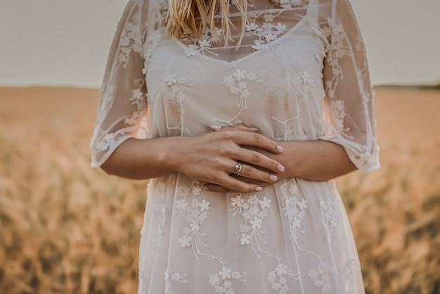 Uma mulher em um vestido de noiva branco justo com uma estampa floral está no meio de amarelo trigo
