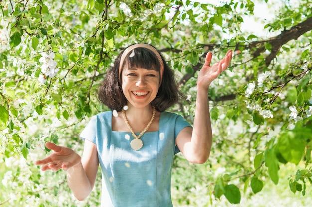 Uma mulher em um vestido longo azul com macieiras em flor no jardim primavera. ela anda no parque e sorri.