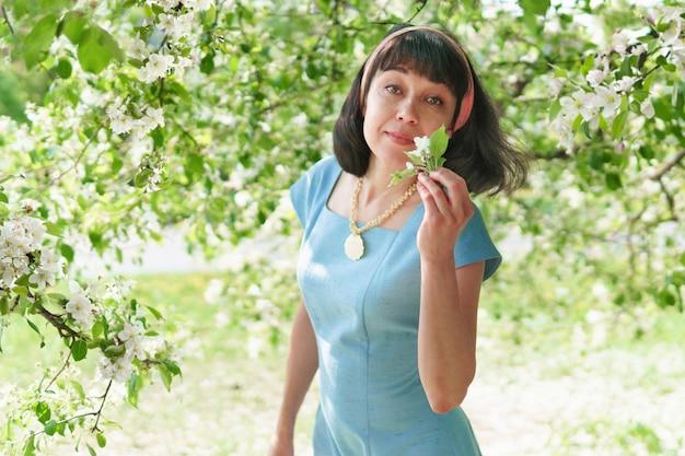 Uma mulher em um vestido longo azul com macieiras em flor no jardim primavera. ela está caminhando no parque.