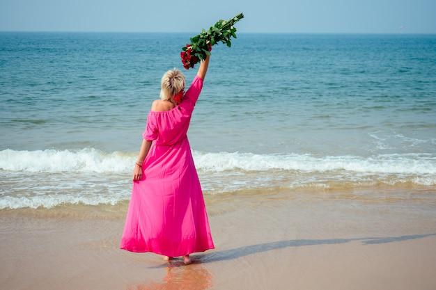 Uma mulher em um vestido longo rosa desfruta de um buquê de rosas doadas na praia