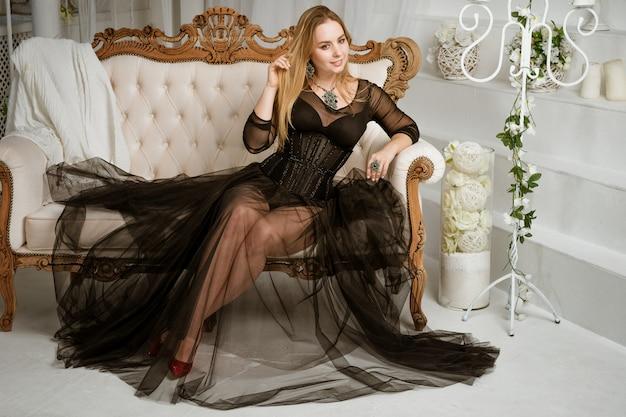 Uma mulher em um vestido preto está sentado em um sofá no interior