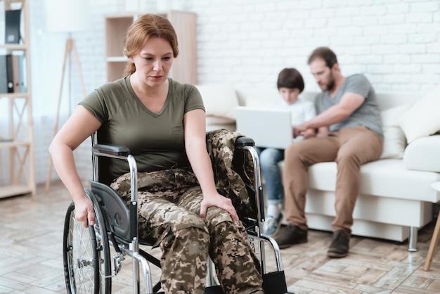 Uma mulher em uma cadeira de rodas está com dor.