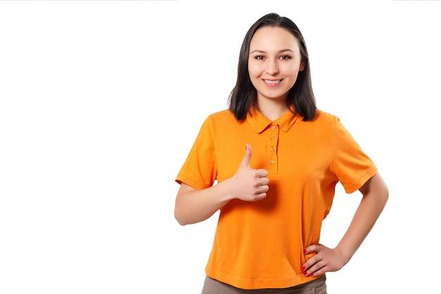 Uma mulher em uma camisa polo brilhante mostra um polegar para cima gesto e sorri