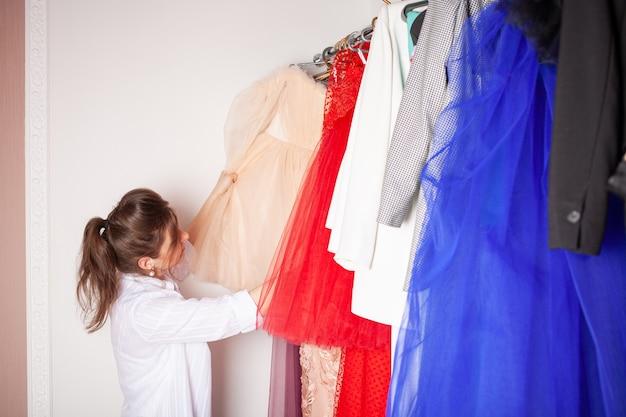 Uma mulher em uma loja de roupas escolhe um vestido