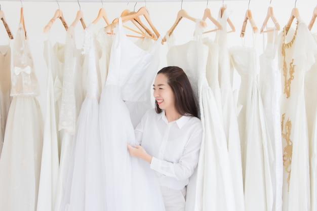 Uma mulher em uma loja de vestidos de noiva está sorrindo enquanto segura seu vestido de noiva.