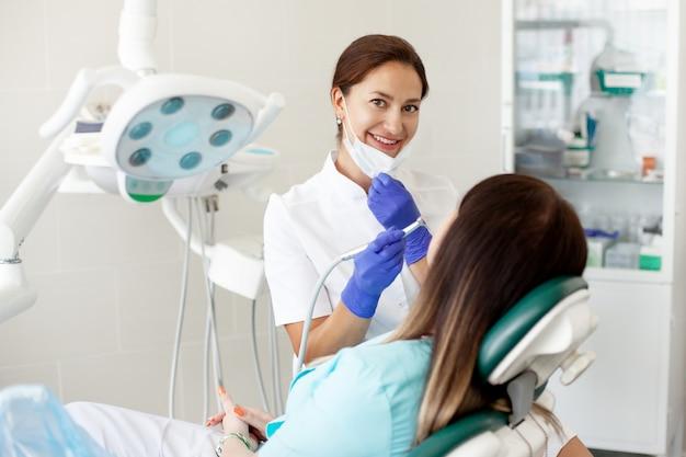 Uma mulher em uma máscara senta-se em uma cadeira odontológica na clínica.