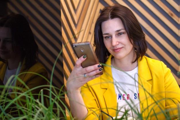 Uma mulher encantadora lê boas notícias em um telefone celular enquanto relaxa em um café