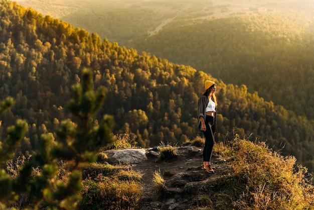 Uma mulher encontra o pôr do sol nas montanhas. o homem viaja nas montanhas. turismo de montanha. a jornada para as montanhas. homem no fundo de uma bela paisagem à noite. copie o espaço