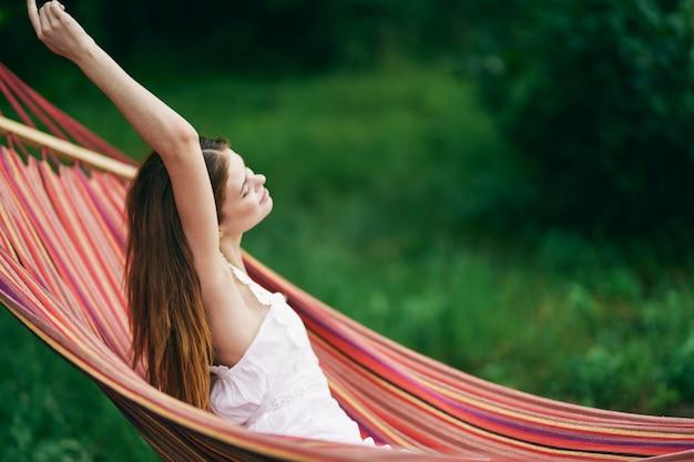 Uma mulher encontra-se numa rede na natureza e está descansando