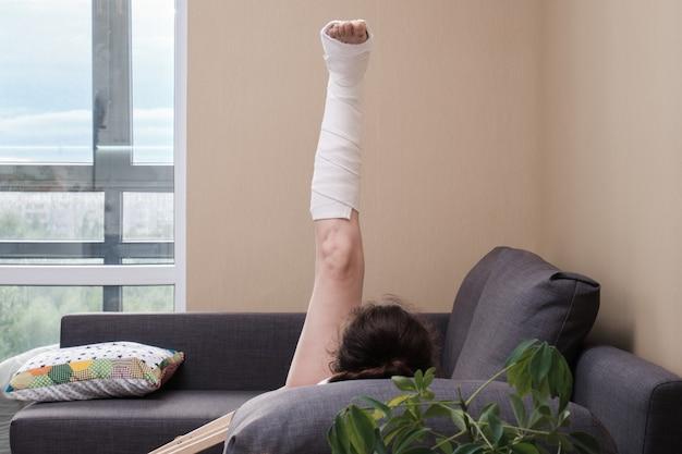 Uma mulher engessada na perna está fazendo exercícios físicos. reabilitação após lesão.