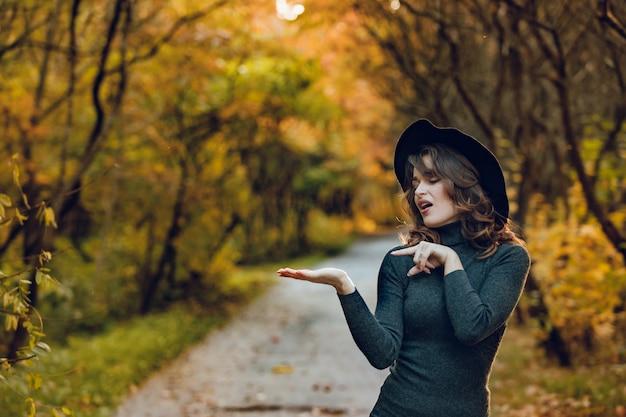 Uma mulher engraçada em um chapéu preto e um vestido verde fica no parque no outono no caminho
