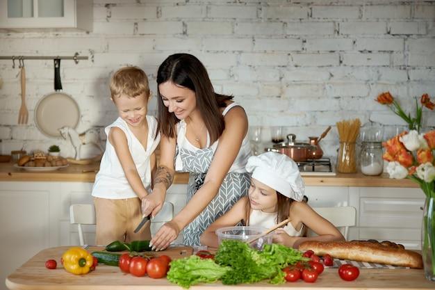 Uma mulher ensina sua filha a cozinhar com seu filho