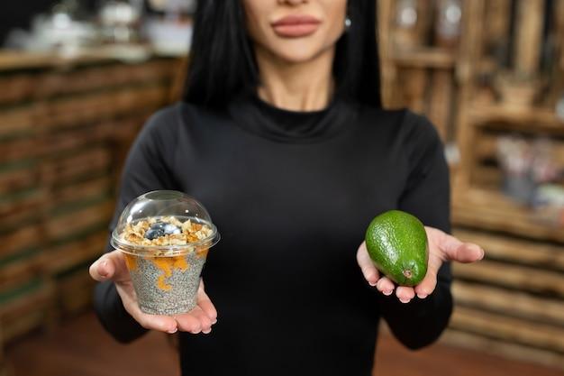 Uma mulher escolhe entre uma sobremesa doce e um abacate saudável