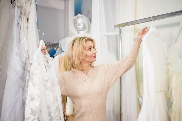 Uma mulher escolhe roupas em um ateliê ou loja.