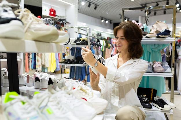 Uma mulher escolhe tênis branco no shopping