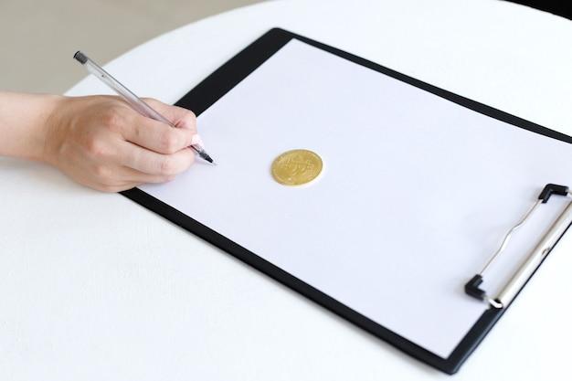 Uma mulher escreve em um tablet com bitcoin. para texto