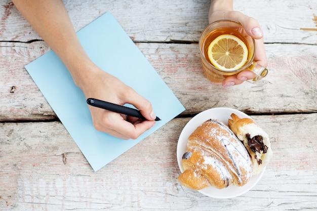 Uma mulher escreve um artigo e bebe chá quente.