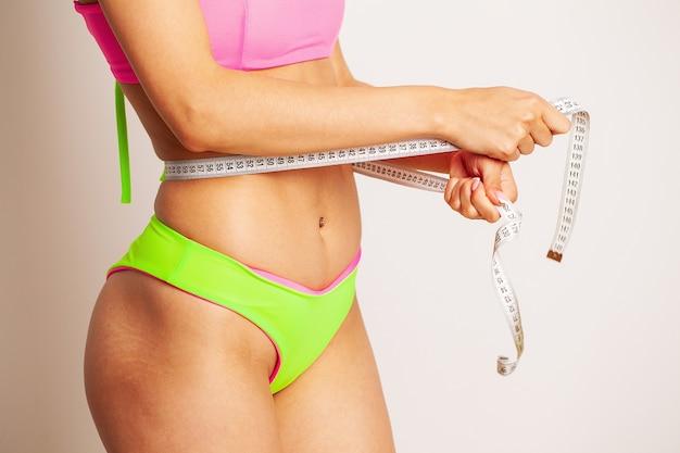 Uma mulher esguia mede o tamanho de sua cintura.
