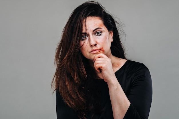 Uma mulher espancada com roupas pretas em uma parede cinza isolada. violência contra a mulher.