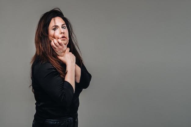 Uma mulher espancada com roupas pretas em uma superfície cinza isolada. violência contra a mulher.