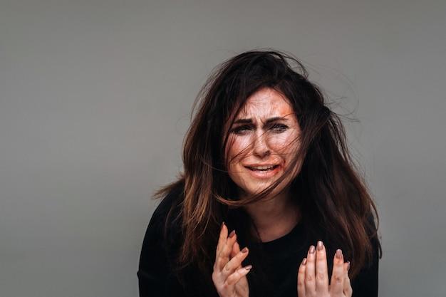 Uma mulher espancada com roupas pretas sobre um fundo cinza isolado. violência contra mulher