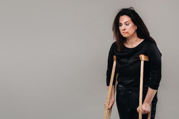 Uma mulher espancada em roupas pretas com muletas nas mãos em um fundo cinza