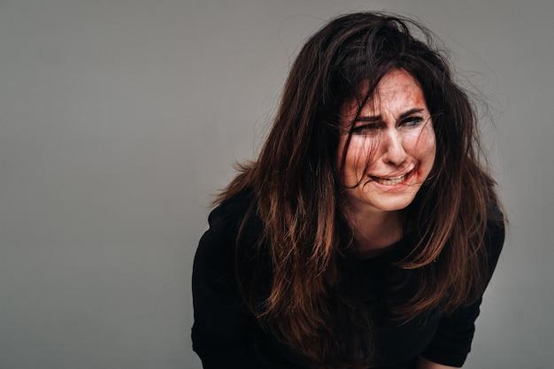 Uma mulher espancada em roupas pretas grita contra um fundo cinza isolado. violência contra a mulher.
