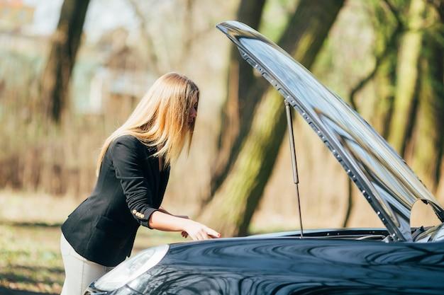 Uma mulher espera por assistência perto de seu carro quebrado na beira da estrada.
