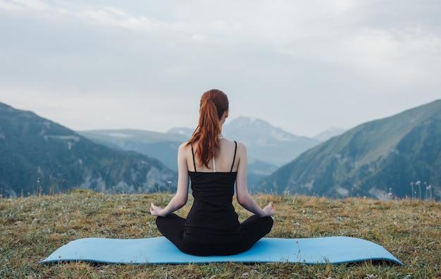 Uma mulher esportiva na natureza está envolvida em ioga em um fundo de montanhas. foto de alta qualidade