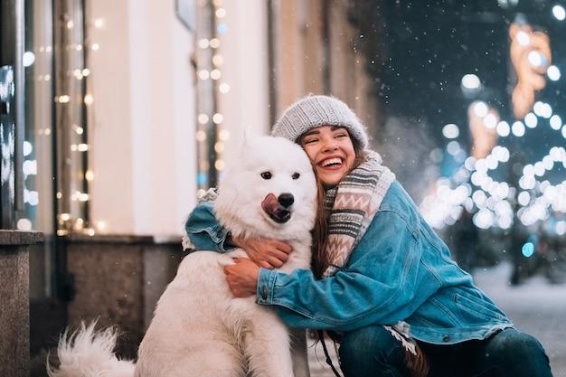 Uma mulher está abraçando seu cachorro em uma rua noturna.