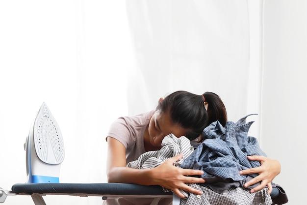 Uma mulher está abraçando uma pilha de roupas. e ferro elétrico branco