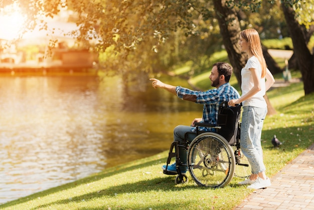 Uma mulher está andando no parque com um homem em uma cadeira de rodas