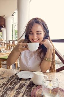 Uma mulher está bebendo cappuccino