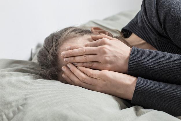 Uma mulher está chorando cobrindo o rosto com as mãos.