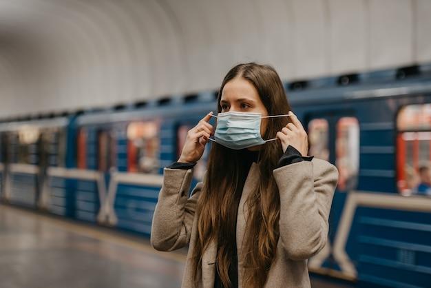 Uma mulher está colocando uma máscara médica no rosto para evitar a propagação do coronavírus em uma estação de metrô. uma garota com cabelo comprido e um casaco bege está esperando o trem em uma plataforma do metrô.