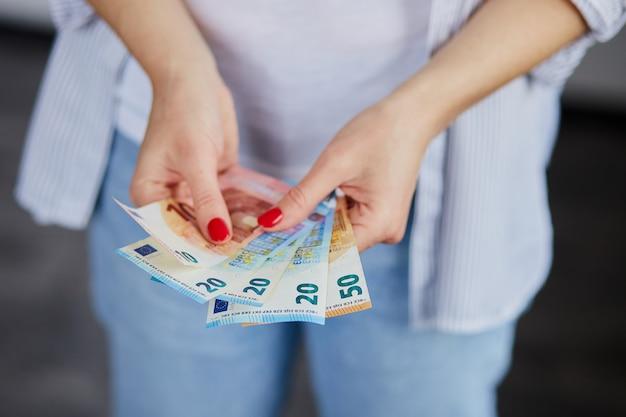 Uma mulher está com dinheiro do euro nas mãos.