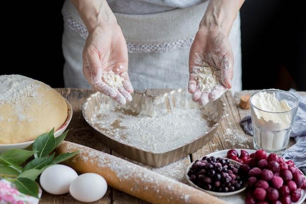 Uma mulher está cozinhando uma deliciosa torta de cereja em casa