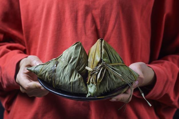Uma mulher está dando zongzi (bolinho de arroz) para os outros como um presente no dragon boat festival,