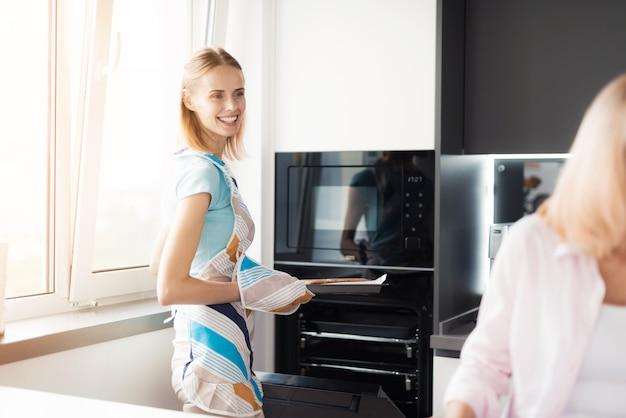 Uma mulher está de pé junto ao forno com uma bandeja nas mãos.