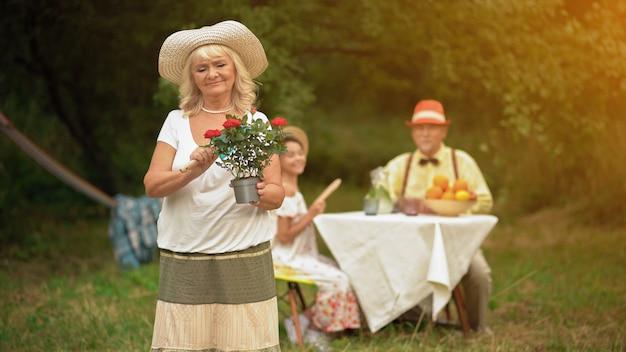 Uma mulher está de pé no jardim segurando um vaso de flores em uma mão e uma colher de jardineiro