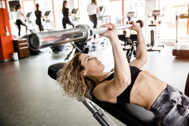 Uma mulher está deitada em um aparelho de treinamento