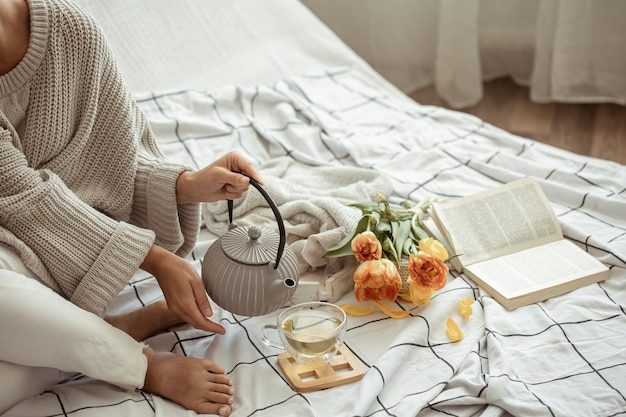 Uma mulher está descansando na cama com chá, um livro e um buquê de tulipas