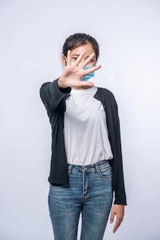 Uma mulher está doente em pé usando uma máscara e sinal de mão proibida