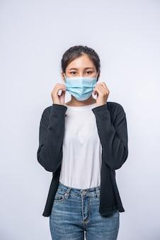 Uma mulher está doente em pé usando uma máscara. use um casaco preto e jeans.