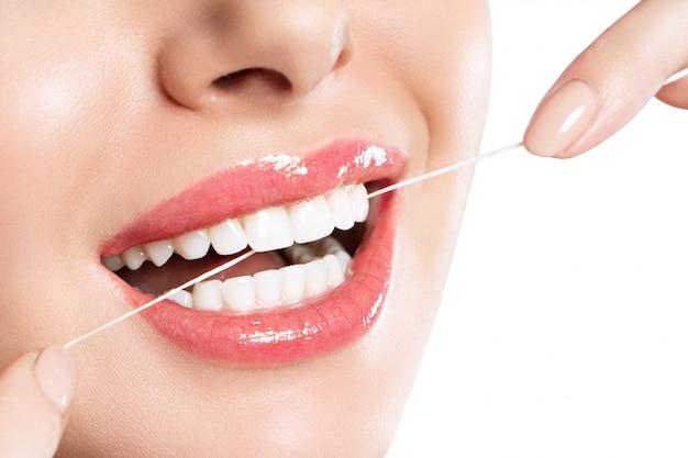Uma mulher está escovando os dentes com fio dental.