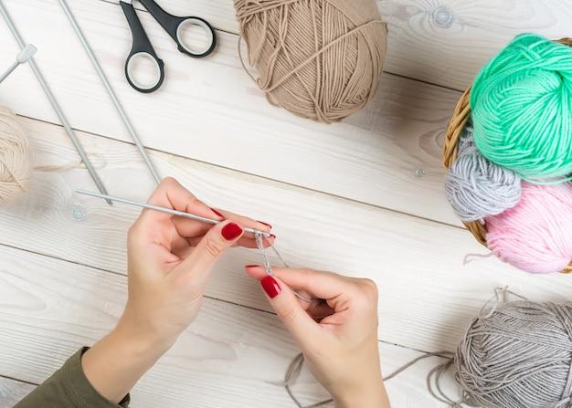Uma mulher está fazendo crochê em uma mesa de madeira branca, com fios coloridos ao redor.